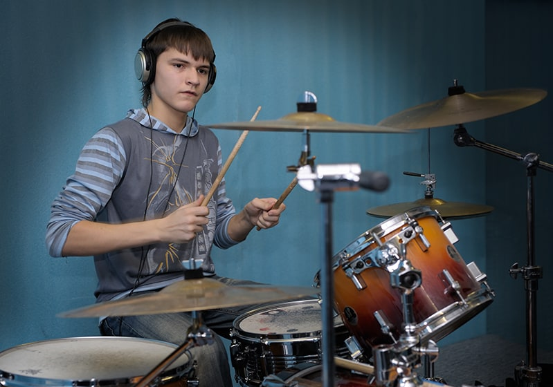 Drum student with headphones playing along to music.